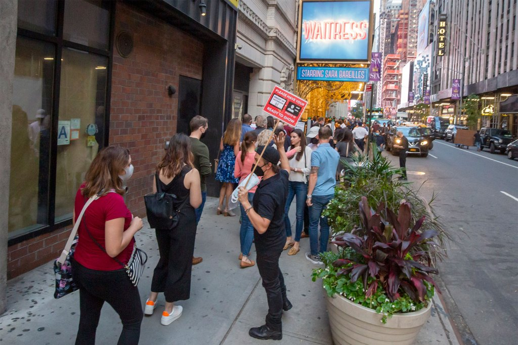 """People wait outside of the Barrymore theater in Times Square to see the musical """"Waitress."""""""
