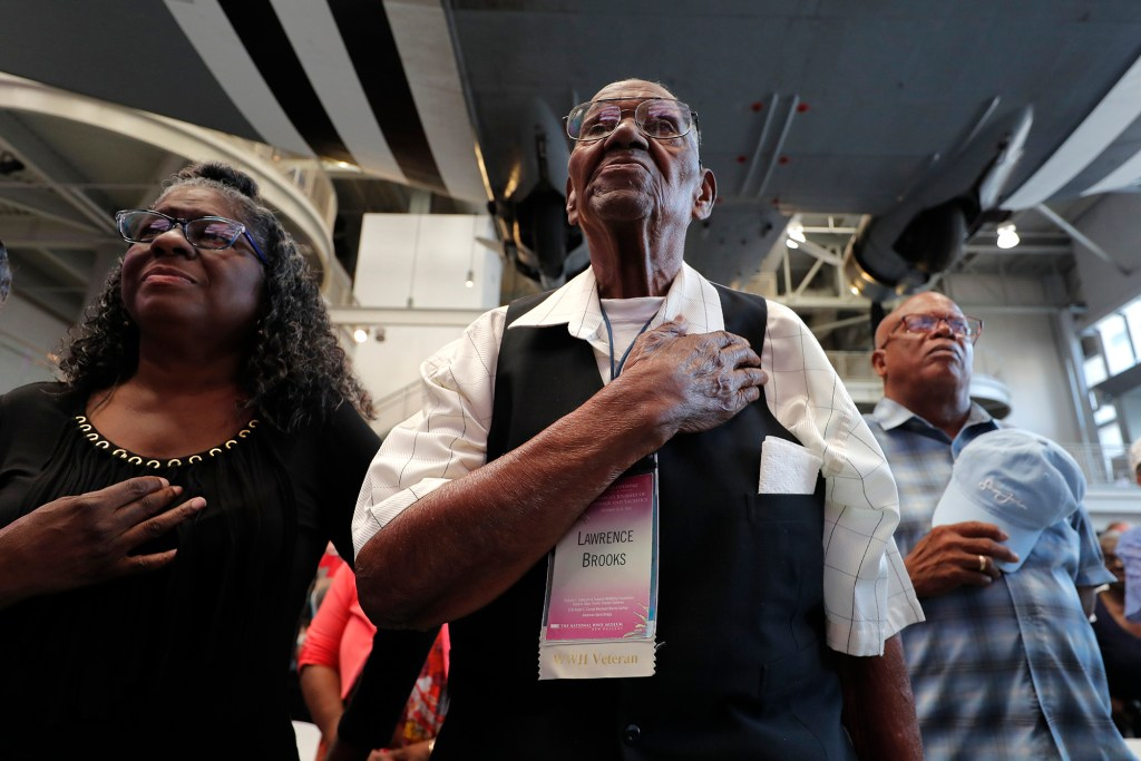 World War II veteran Lawrence Brooks holds his hand to his heart during the singing of the National Anthem as he celebrates his 110th birthday at the National World War II Museum in New Orleans, Thursday, Sept. 12, 2019.