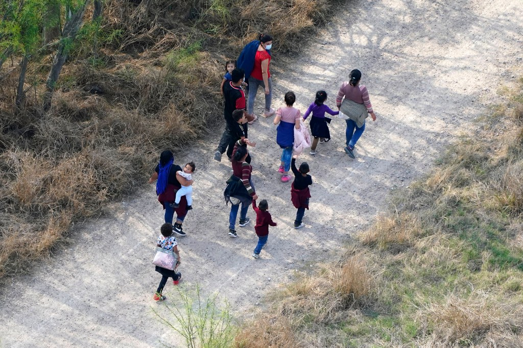 Migrants walk on a dirt road after crossing the U.S.-Mexico border
