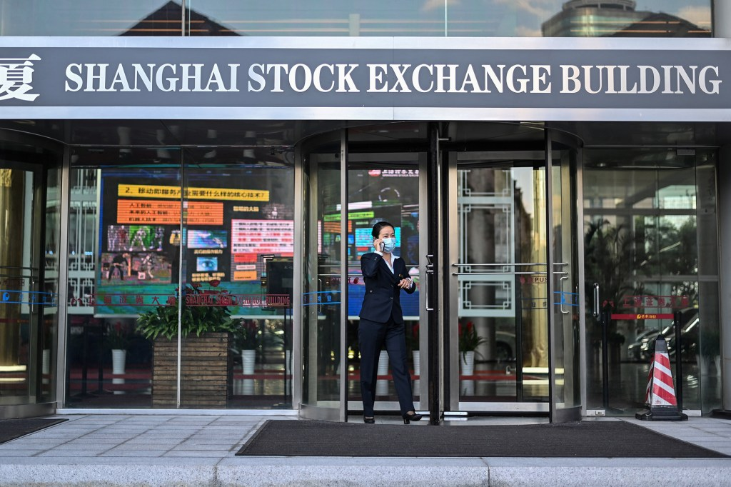 A woman leaves the Shanghai Stock Exchange building