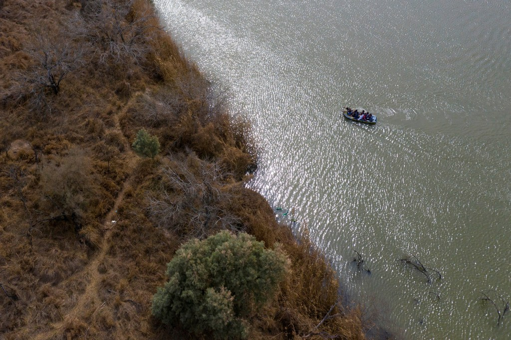 Smugglers use a raft to transport migrant families and children across the Rio Grande River into the United States from Mexico in Penitas, Texas.