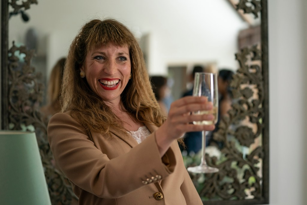 Photo showing Daisy Haggard as Miri, wearing a nice outfit and holding a glass of champagne.
