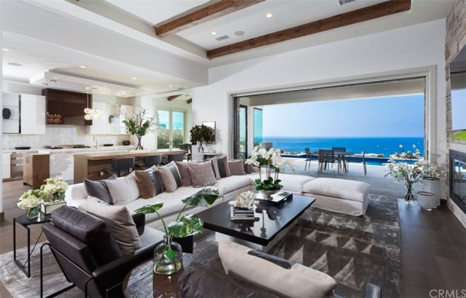 The quarter-acre lot overlooks the Pacific Ocean and offers a pool, hot tub, fire pit and outdoor seating and dining areas.