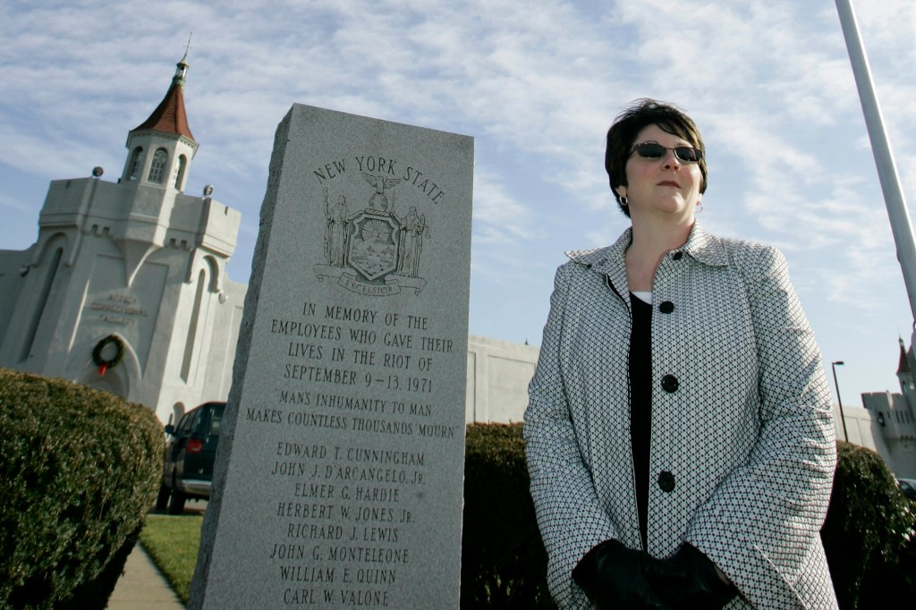 Deanne poses by a memorial for the prison employees, including her father, William Quinn.