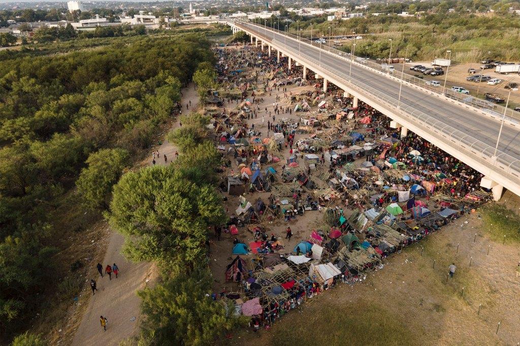 Migrants are seen at an encampment along the Del Rio International Bridge near the Rio Grande.