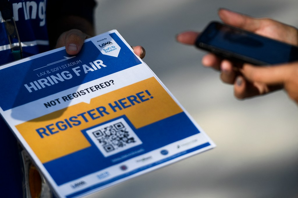 A person scans a QR code with their phone to register for a job fair