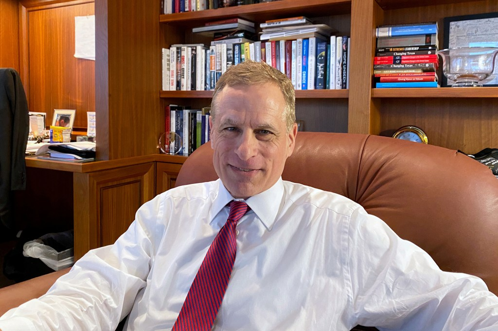 Robert Kaplan sitting in a leather office chair behind a desk with bookcases behind him