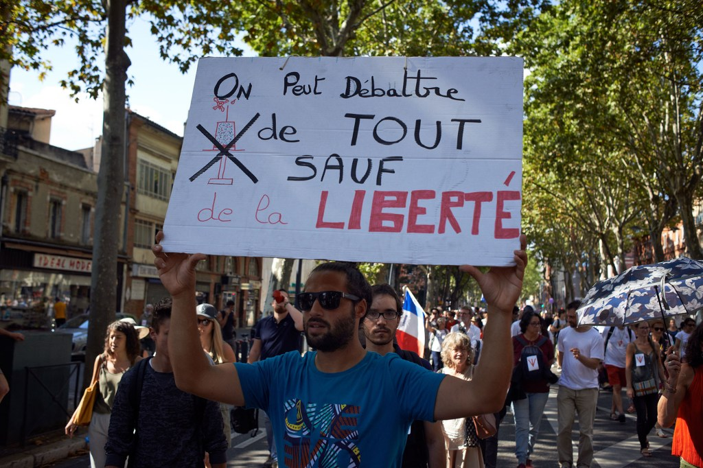 A protester displays a cardboard reading 'We can discuss everything excep Liberty'. Several thousands of  protesters took to the streets in Toulouse against the near mandatory vaccination and against the mandatory health pass after Macron's speech on July 12th.
