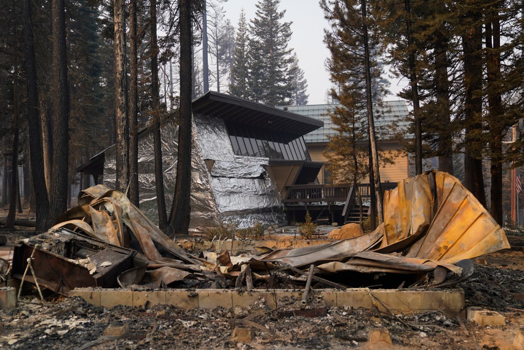 A cabin partially covered in fire-resistant material stands behind a property destroyed in the Caldor Fire in Twin Bridges, California.