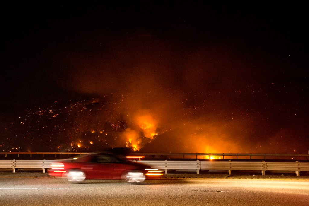 A car drives past the Route Fire on Interstate 5.