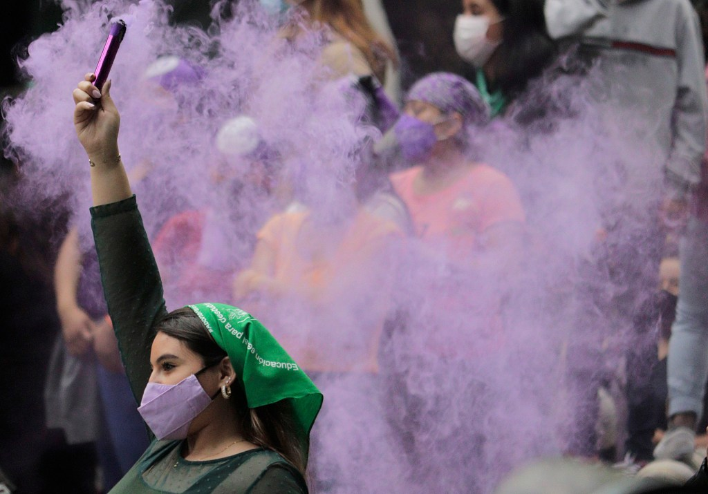 A woman holds a flare as she marches from the Angel of Independence to the Zocalo in Mexico City for the Global Day of Action in favour of legal, free and safe abortion in Mexico and Latin America. During the march, there were clashes between demonstrators and police along the route.