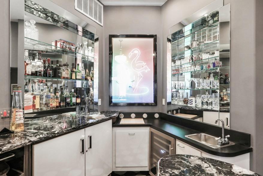 The bar has mirror backsplashes and black countertops.