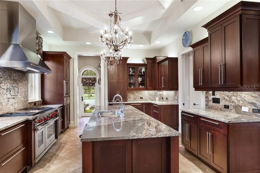A gourmand's kitchen featuring Sub-Zero, Wolf and Miele appliances, oversized granite island, and a walk-in pantry.