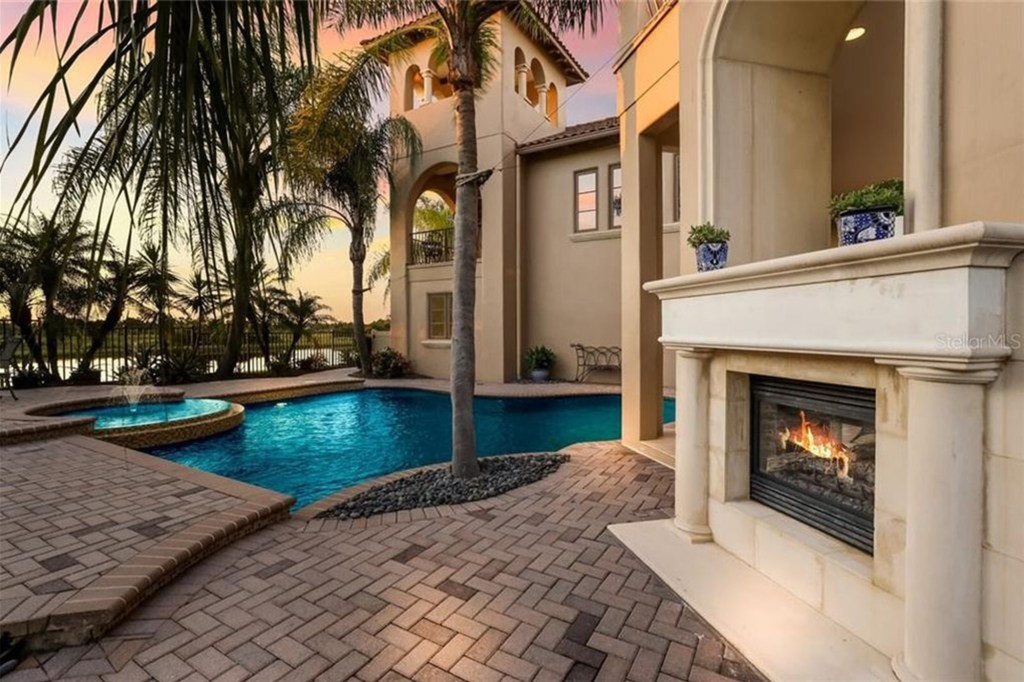 Outdoor spaces features wood-burning fireplace.