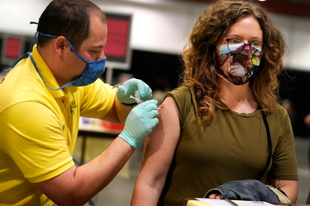 Nicole Torres, right, receives Pfizer's COVID-19 vaccine from Ryan McCrea, left, from Las Vegas, at the Music City Center convention facility Friday, March 12, 2021.