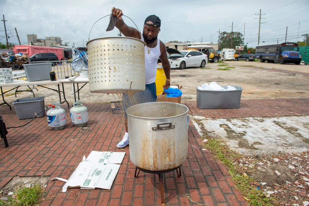 Demon Vernon pulls up a pot of boiling seafood as he and others cook and serve food at the site of a former McDonalds at the corner of Morrison and Dowman roads, Wednesday, Sept. 8, 2021, in New Orleans East.