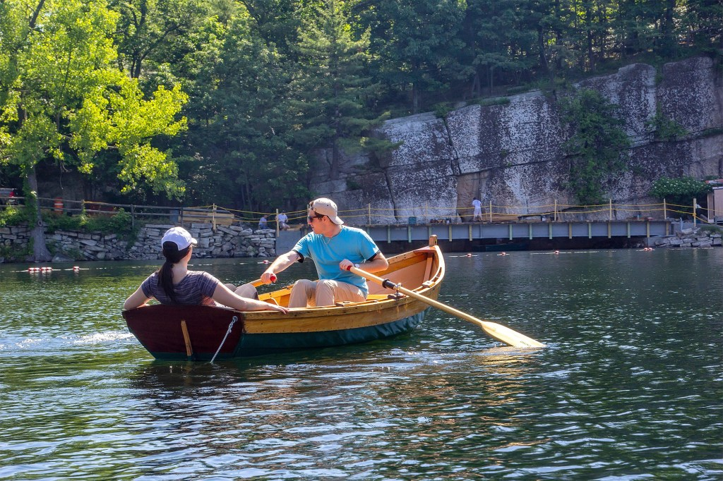 Young couple navigate a row boat in Lake Mohonk, a Victorian style hotel nestled in the Shawangunk Mountains.
