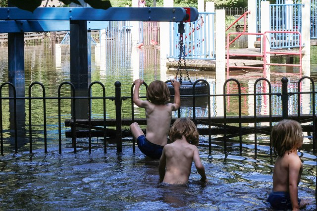 Twins Rasmus and Peter Meyer Rader, 5, and their friend, Linus Bonet Demming, 4, explore a flooded area surrounding a park after the remnants of Tropical Storm Ida.