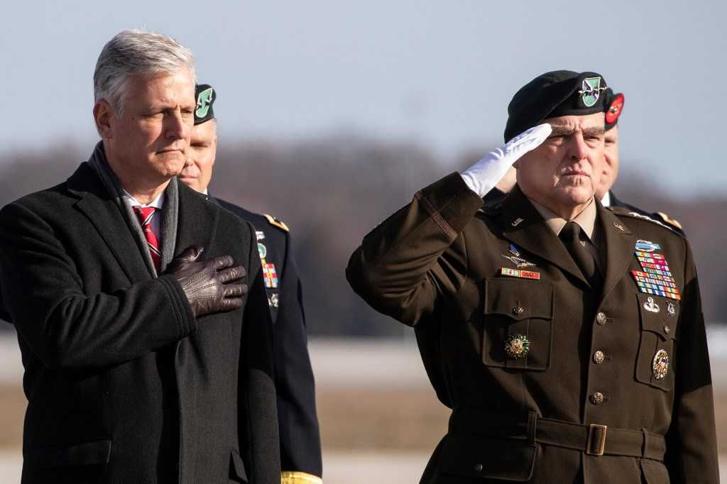 Acting Under Secretary of the Army James McPherson, left, National Security Adviser Robert O'Brien, Joint Chiefs Chairman Gen. Mark Milley and others, stand as an Army carry team moves a transfer case containing the remains of U.S. Army Sgt. 1st Class Michael Goble, Wednesday, Dec. 25, 2019, at Dover Air Force Base, Del.