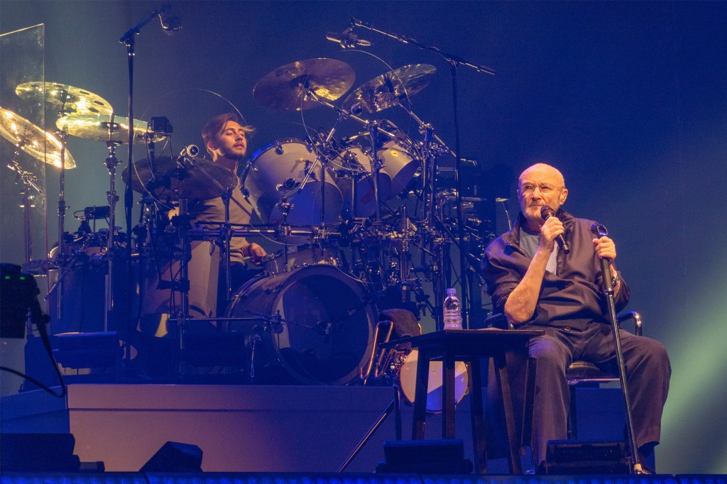 Rock legend Phil Collins received a standing ovation as he sat down to sing for the first night of the Genesis reunion tour.