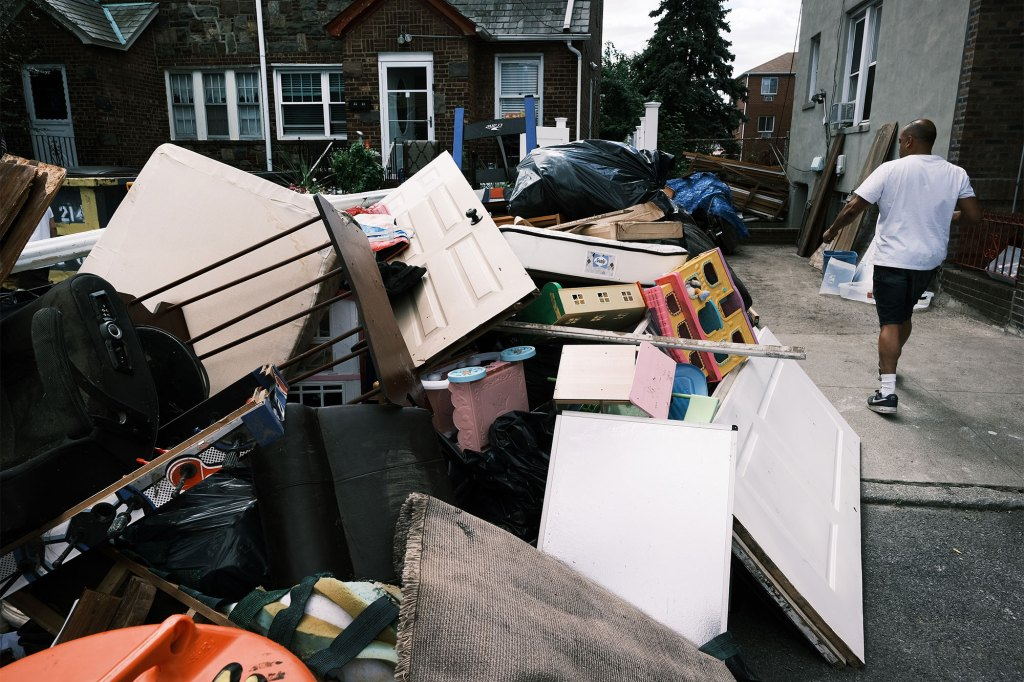 A person sorts through belongings from their flooded home in a Queens neighborhood.
