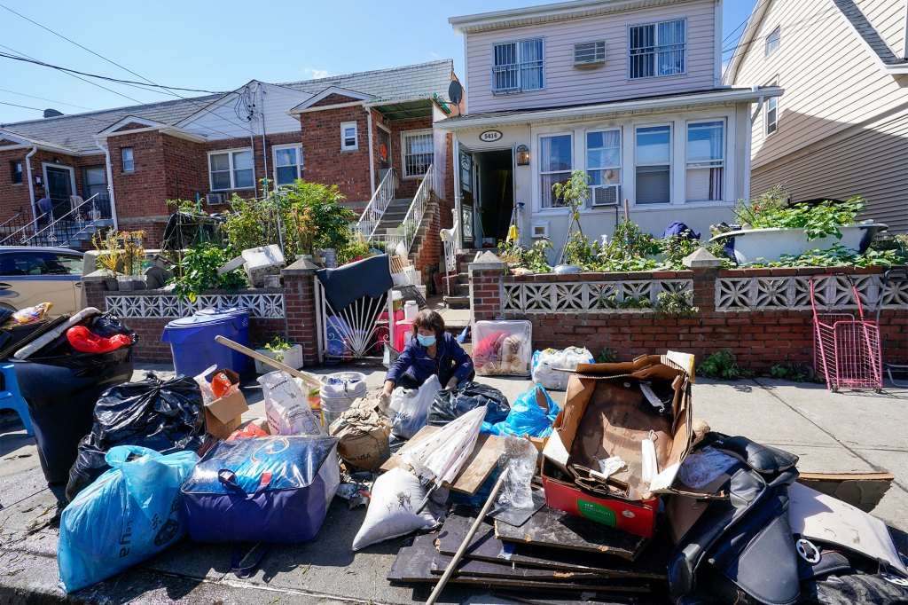 A resident in the Flushing neighborhood of the Queens borough of New York sorts through her water logged belongings.
