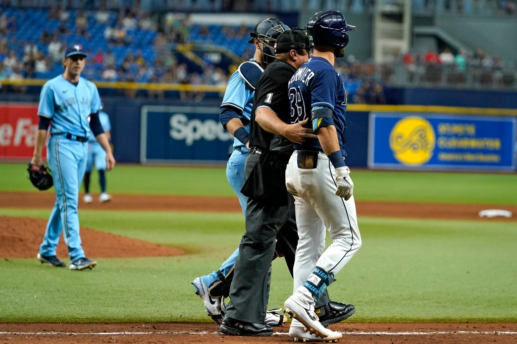 Rays' Kevin Kiermaier is held back by home plate umpire Bruce Dreckman and Toronto Blue Jays catcher Danny Jansen after Kiermaier was hit with a pitch by starting pitcher Ryan Borucki.