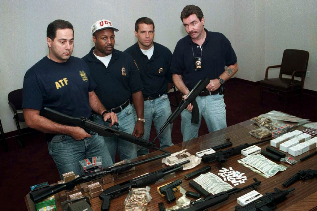 (Left to right) ATF agent Sam Rabadi and NYPD Detectives Wendell Stradford, John Dove and Patrick Lanigan seize guns and cash during an arrest in Staten Island on August 30, 1996.