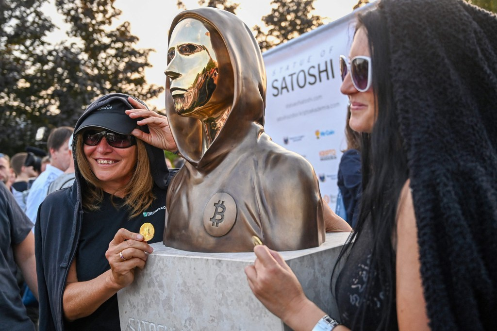 Fans pose for a photo with the statue of Satoshi Nakamoto after its unveiling at the Graphisoft Park in Budapest.