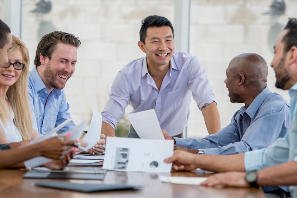 Group of business people meeting together, featuring Simu Liu