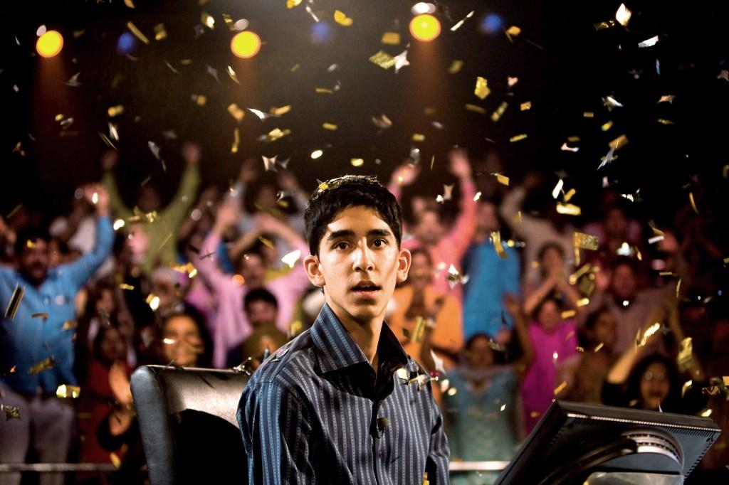 "Dev Patel in ""Slumdog Millionaire"" stands in a cheering crowd while confetti rains down around him."