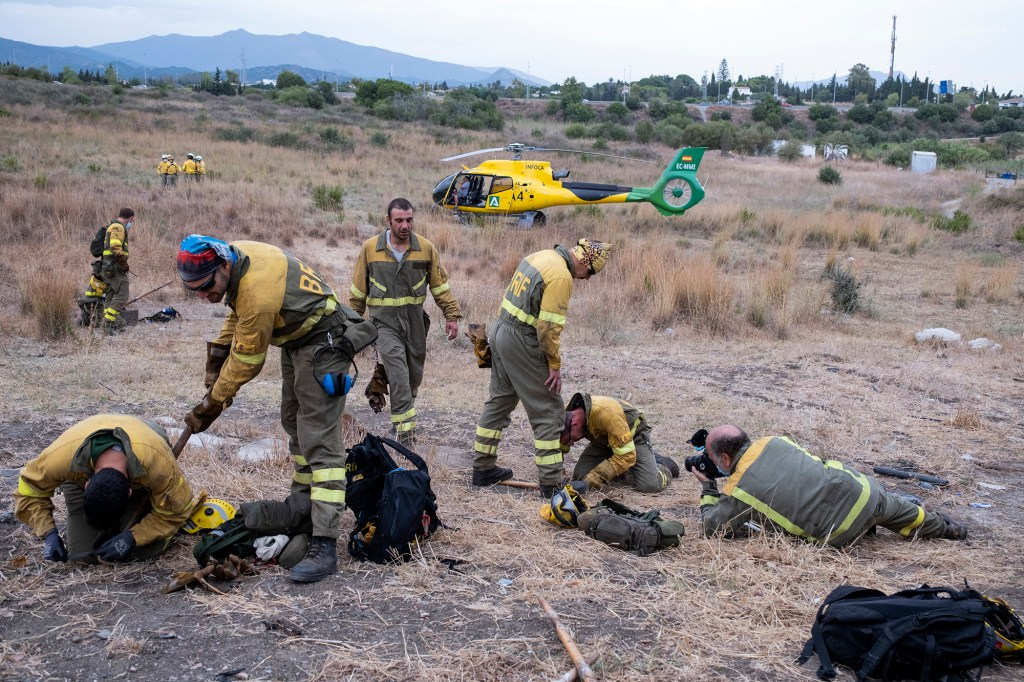 Forest firefighters prepare their equipment before boarding the helicopter to work on extinguishing a wildfire near the town of Jubrique, in Malaga province, Spain, Monday, Sept. 13, 2021.