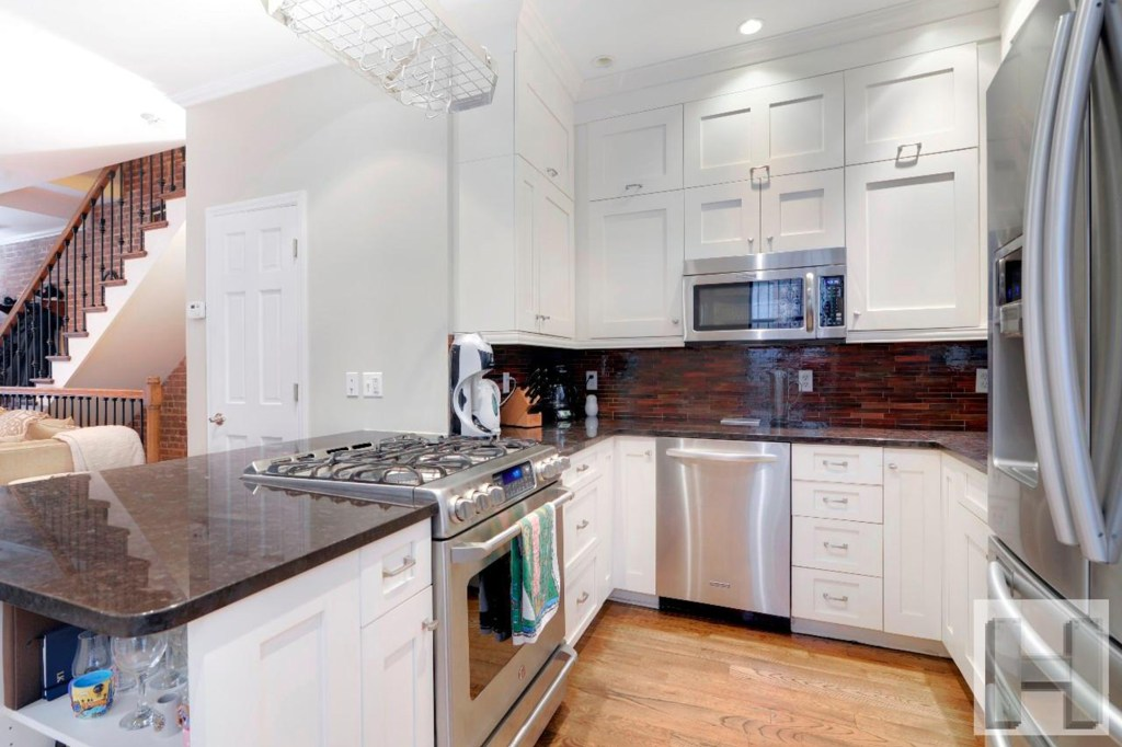 The eat-in kitchen has shiny appliances and granite counters.