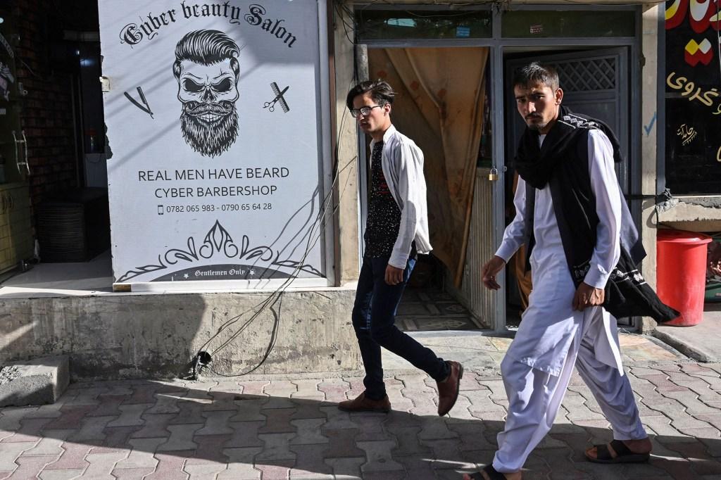 Men walk past a barbershop in Kabul.