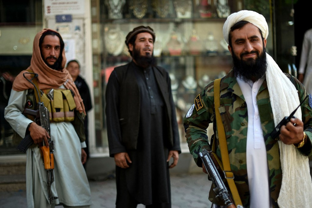 Taliban fighters stand guard.