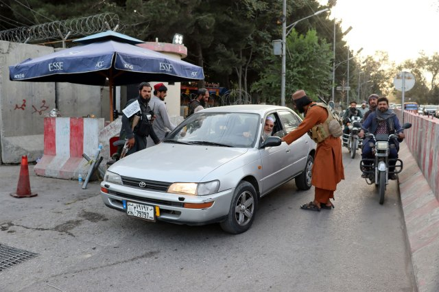 Taliban militants searching a car at a checkpoint in Kabul, Afghanistan on August 25, 2021.