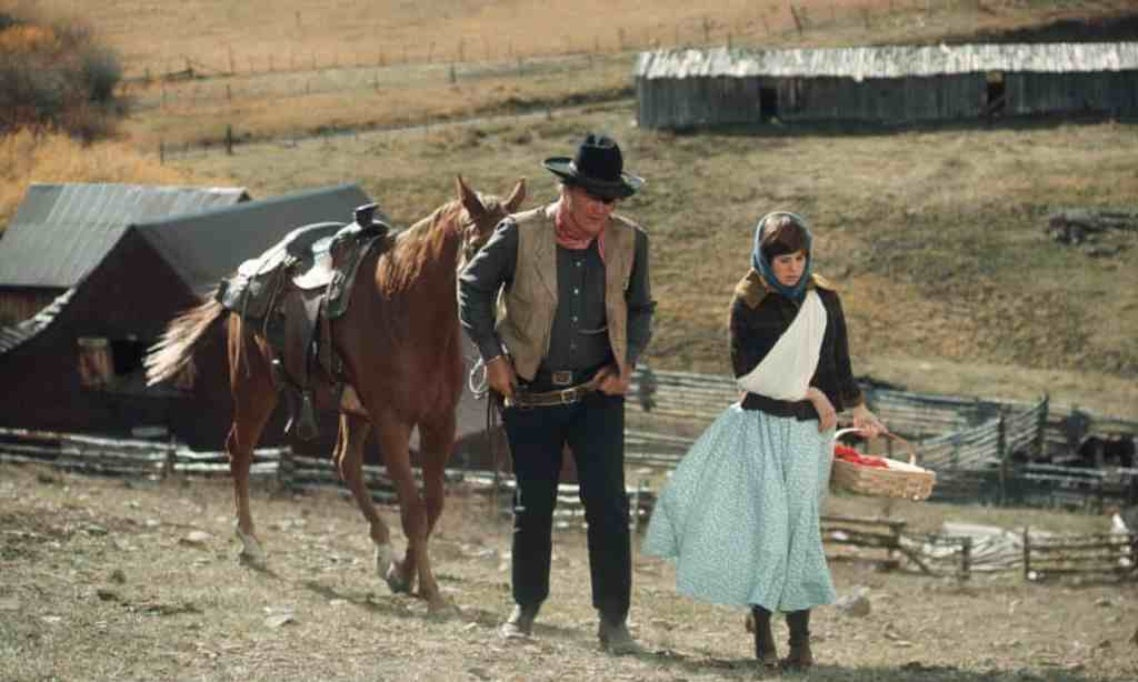 "John Wayne and Kim Darby on set of the film ""True Grit."""