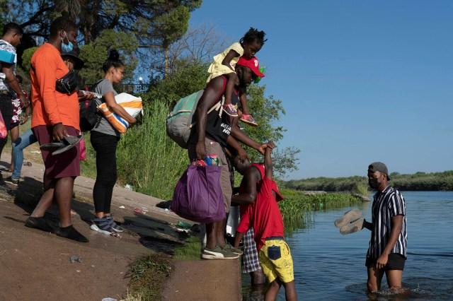 Migrants seeking asylum in the U.S. walk in the Rio Grande river near the International Bridge between Mexico and the U.S