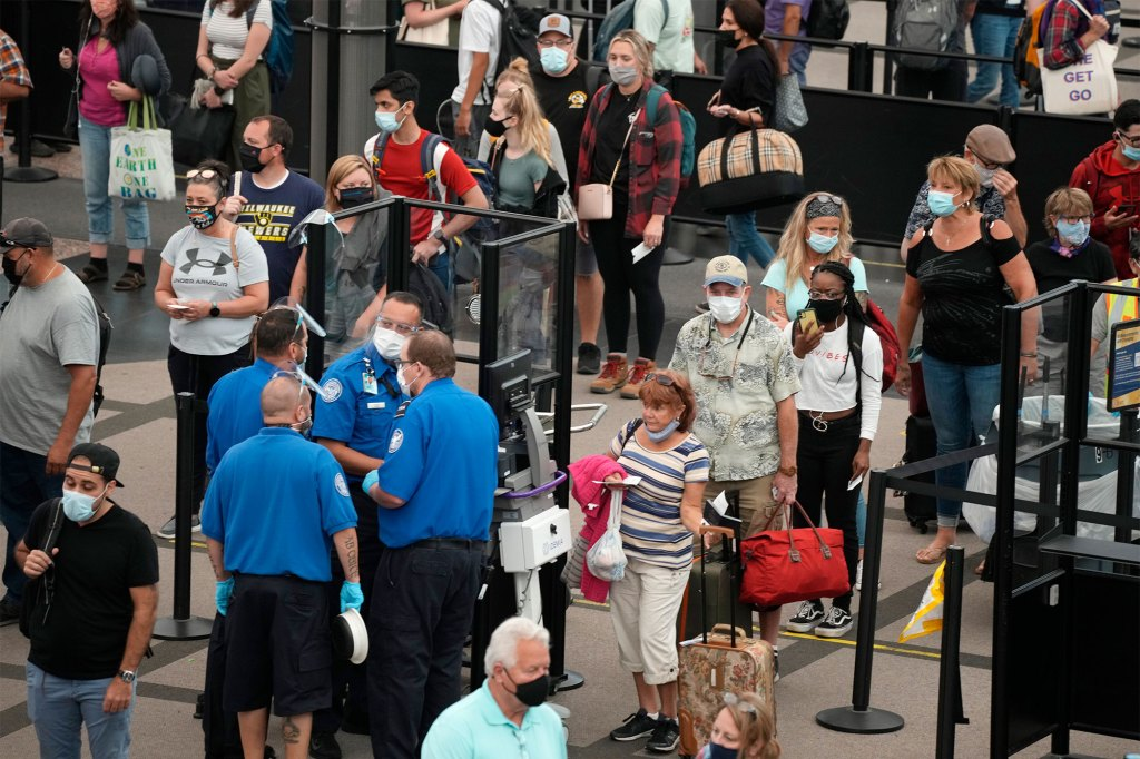 Travelers wear masks at a security checkpoint in the main terminal of Denver International Airport in Denver, Colorado on August 24, 2021.
