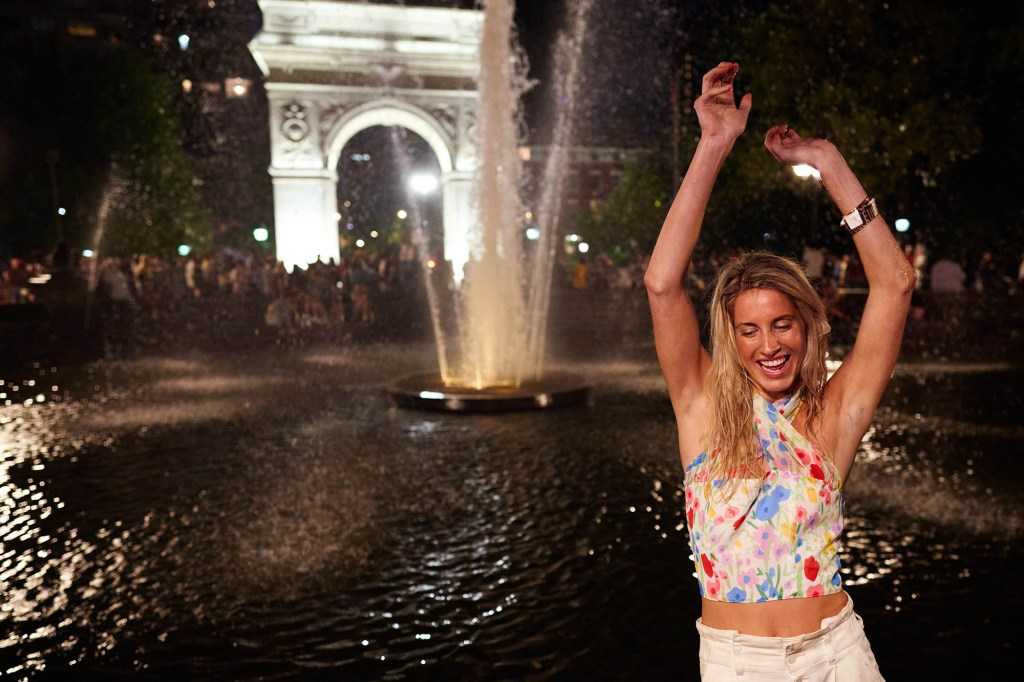 A woman dances in the Washington Square Park fountain on Friday, June 25, 2021