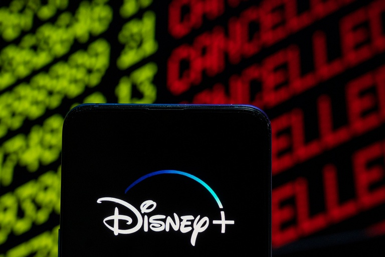 A smartphone with the Disney+ image. The background shows the board at the stock market.