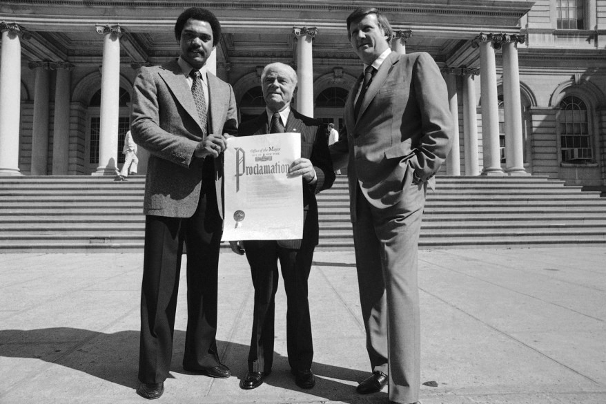 New York Yankee slugger Reggie Jackson, right, holds proclamation which New York Mayor Abe Beame, center, has just presented to Yankees owner George M. Steinbrenner, Wednesday, Sept. 28, 1977 at City Hall in New York.