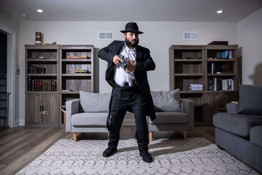Rabbi Raziel Cohen, 24, demonstrates his concealed carry of a Glock 19 under his Kapote