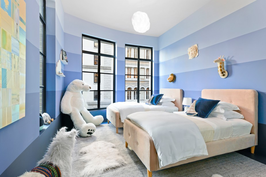 A stuffed bear sits vigil over a double bedded kid's room.