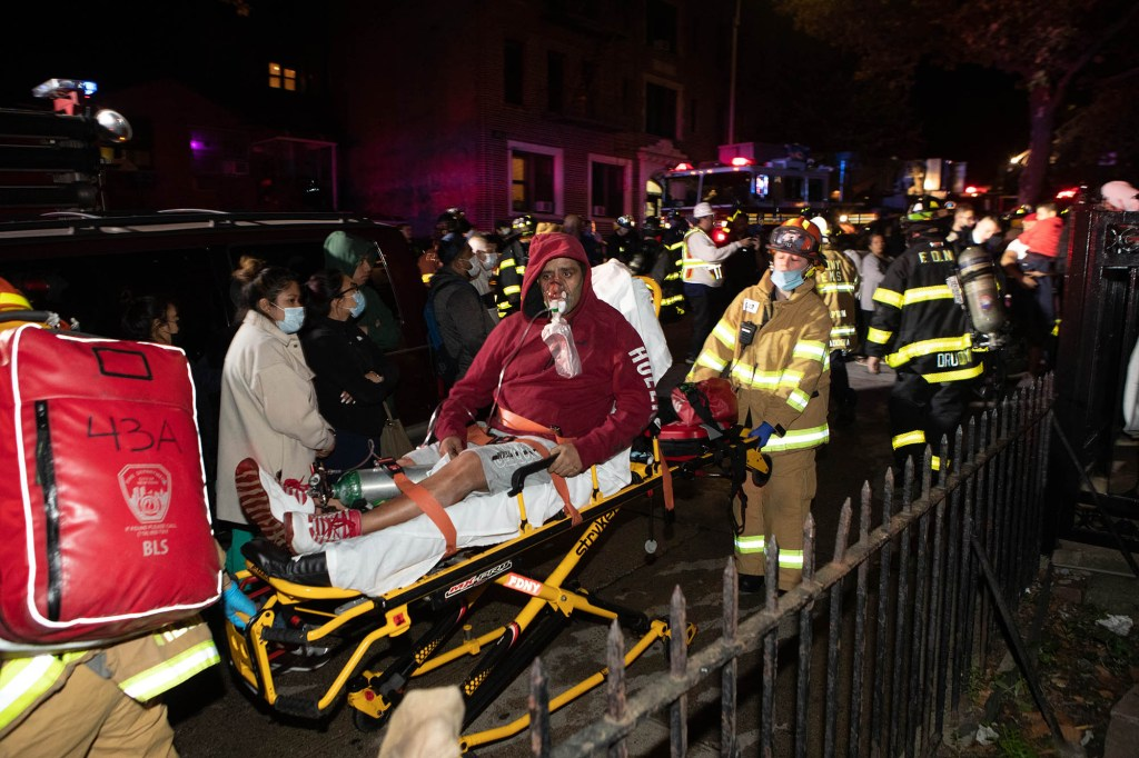 FDNY firefighters escort a man outside of the building on a stretcher.