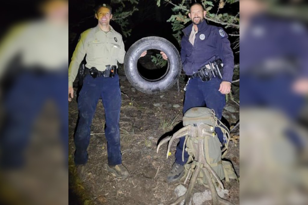 Colorado Wildlife officers Scott Murdoch (left) and Dawson Swanson hold the tire that was trapped inside the bull elk's neck for two years.