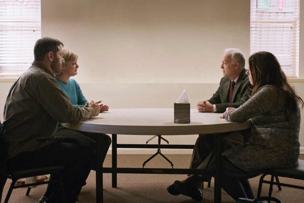 Photo showing Jason Isaacs and Martha Plimpton as Jay and Gail seated across the table from Linda and Richard, played by Ann Dowd and Reed Birney.