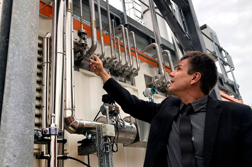 Dietrich Brockhagen, Executive Director of Atmosfair, points on pipes of the system that brings hydrogen and carbon into the facility that mix them and produce e-fuel at the 'Atmosfair' synthetic kerosene plant in Werlte, Germany, Monday, Oct. 4, 2021.