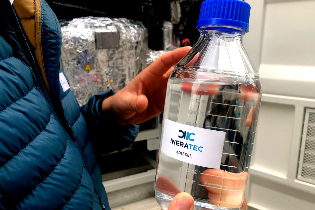A person holds a bottle with e-fuel at the 'Atmosfair' synthetic kerosene plant in Werlte, Germany, Monday, Oct. 4, 2021.
