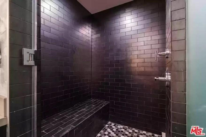 A black tile shower is pictured.
